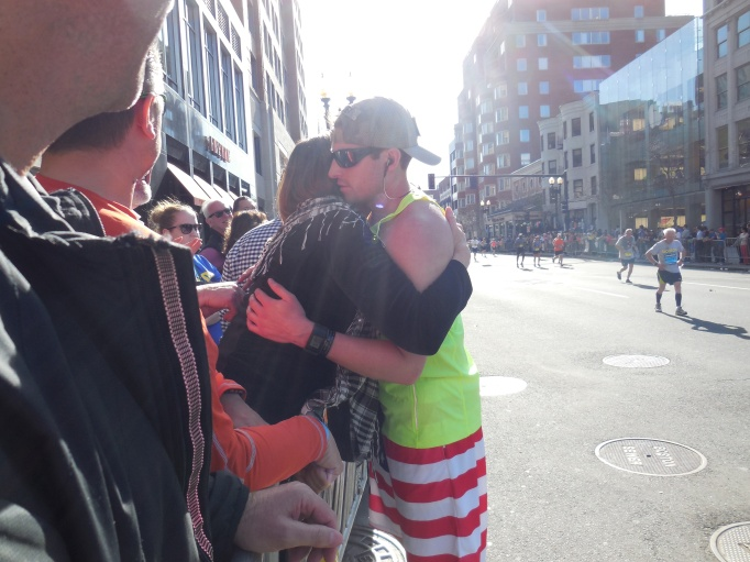 A mom hugging her son as he is about to cross the finish line.  He was running for Team Spalding Rehab